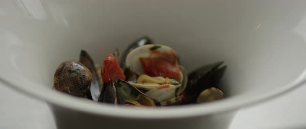 Static shot of a person adding sauce to a bowl of sauteed mussels with tomatoes Royalty-free stock video