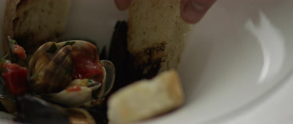 Hand-held shot of a person sticking grilled bread into a bowl of sauteed mussels Royalty-free stock video
