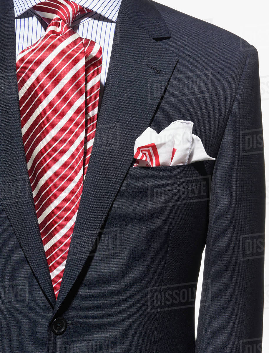 f129b16ea5 Detail of a dark blue suit jacket with red and white striped necktie and  handkerchief and striped shirt
