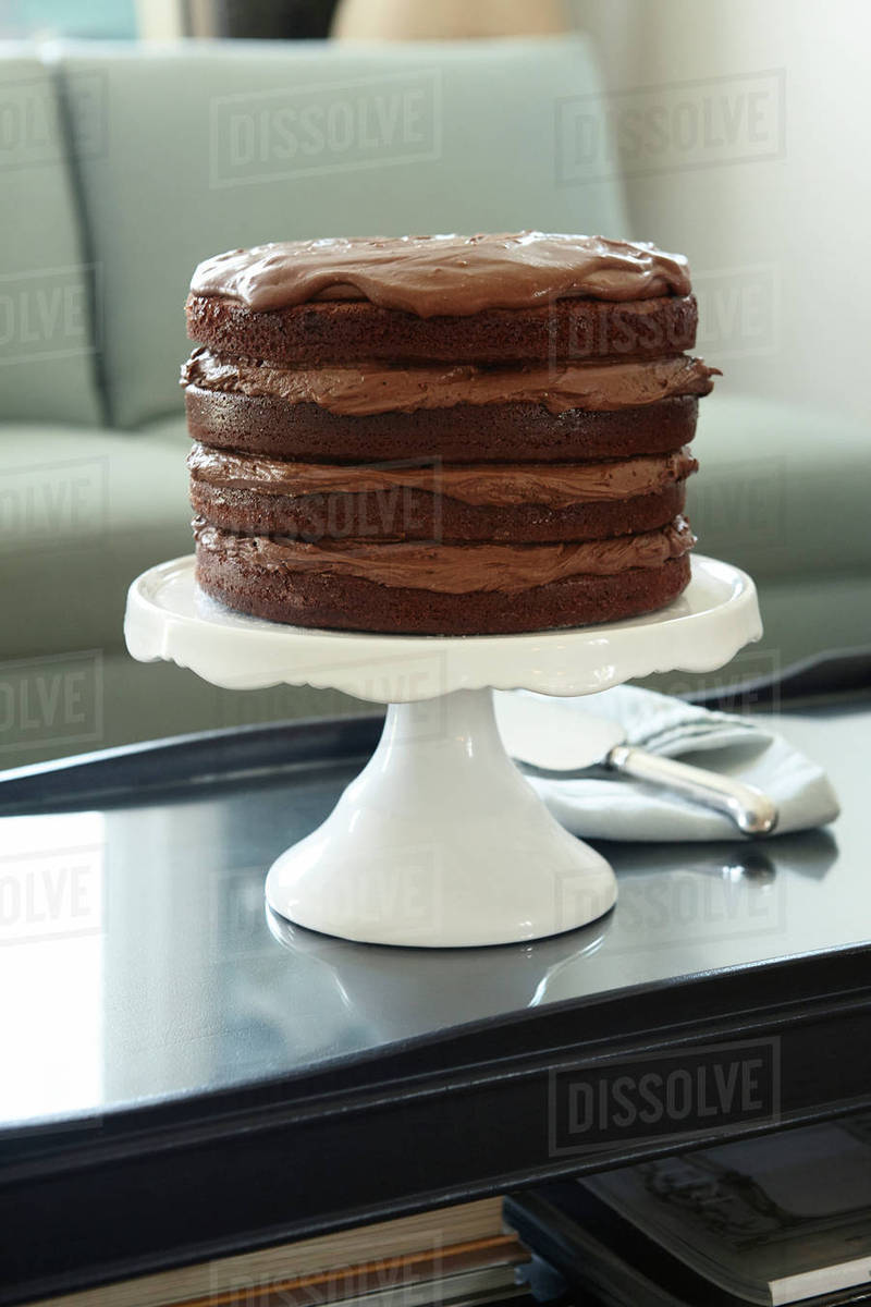 Layered Chocolate Birthday Cake on Cake Stand on Coffee Table ...