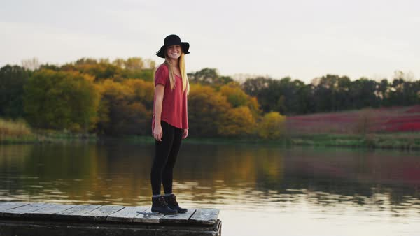 Young, pretty, millennial woman wearing a floppy hat, walks along a dock at a lake  at sunset; she gazes across the water. Royalty-free stock video