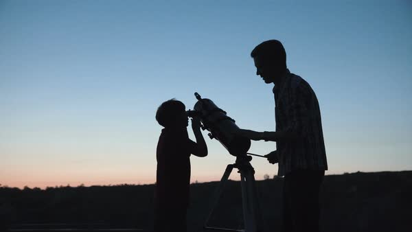Silhouettes of a man with little boy looking through telescope in twilight. Royalty-free stock video