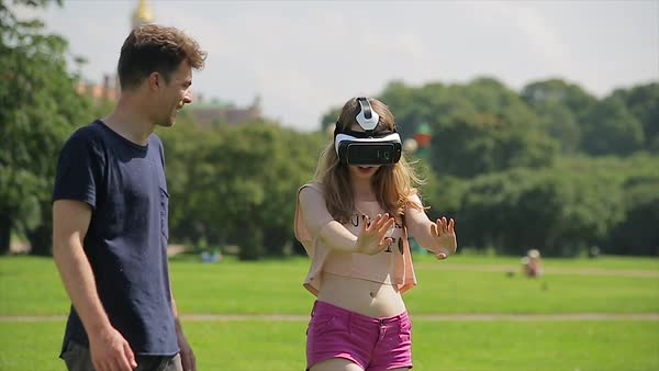 Young woman wearing virtual reality goggles in the park with her boyfriend Royalty-free stock video