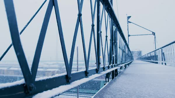 Snowfall covers a walking bridge over train tracks. Royalty-free stock video