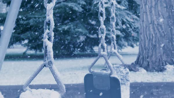An empty swing sways in the midst of a heavy snowstorm. Royalty-free stock video