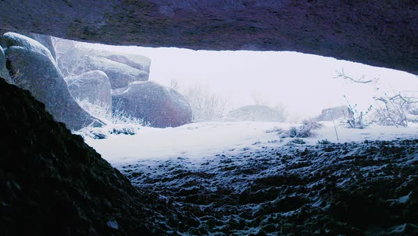 Looking out at snow covered ground from a rock shelter. Royalty-free stock video