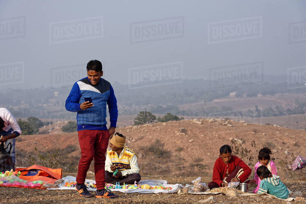 An Indian man is smiling with cellphone in a rural hilltop fair. Royalty-free stock photo