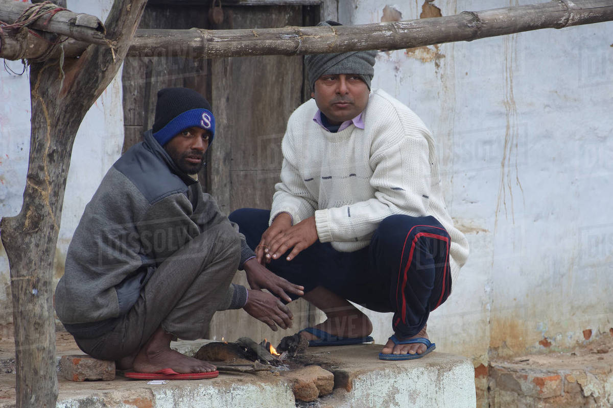 Two Indian poor men are comforting themselves by wood-fire in winter Royalty-free stock photo