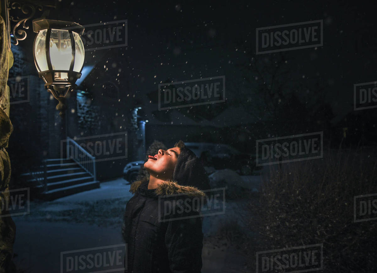 Boy catching snowflakes on his tongue beside a light on a snowy night Royalty-free stock photo