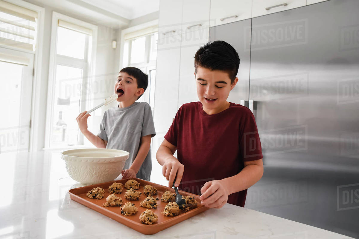 Two happy boys making homemade cookies in a modern white kitchen Royalty-free stock photo