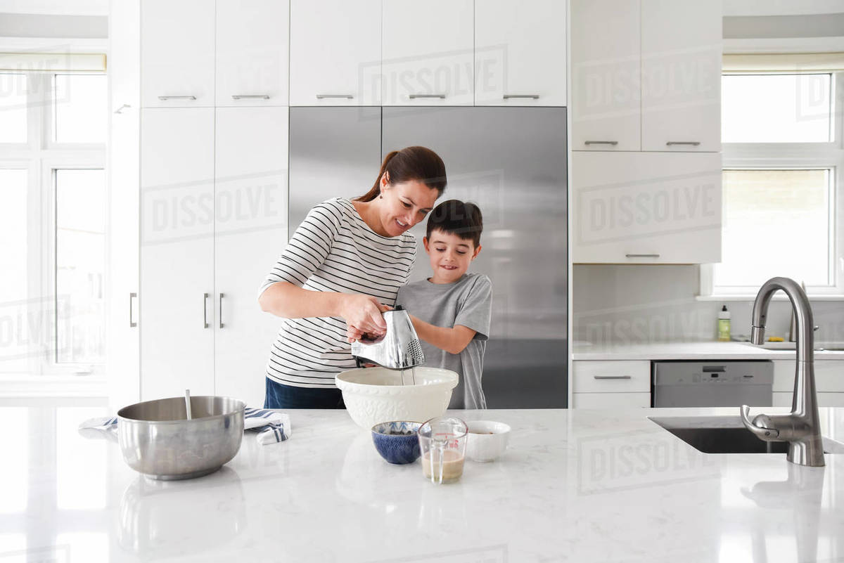 Mother helping young son use a mixer while cooking in a modern kitchen Royalty-free stock photo