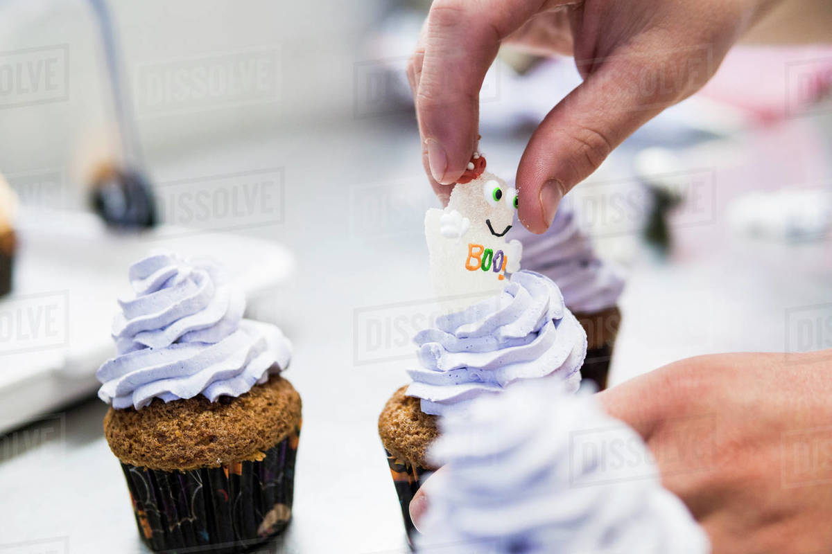 Hand of pastry chef add a sweet sugar ghost on an halloween cupcake Royalty-free stock photo