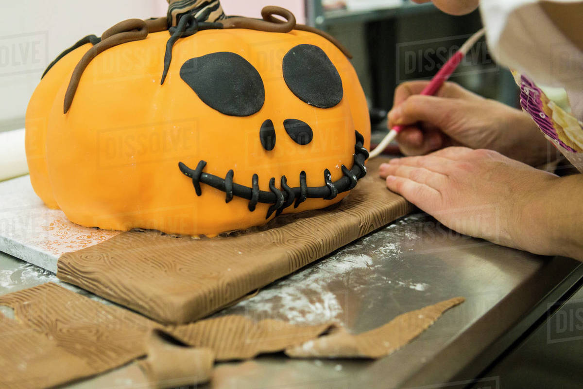 Pastry chef is molding a cake with pumpkin shape Royalty-free stock photo