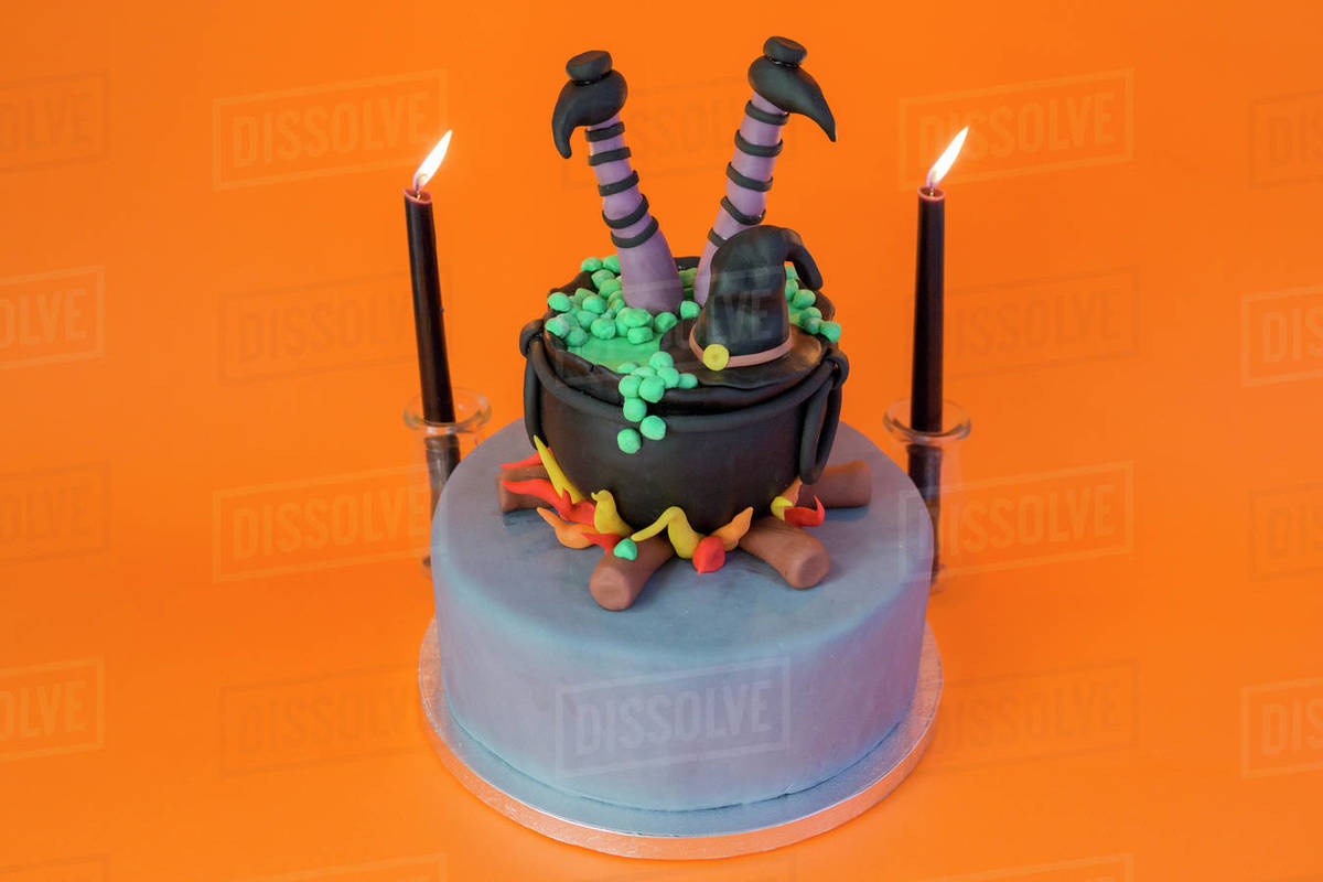 Funny sugar cake with witch inside a pot and candle on a orange table Royalty-free stock photo