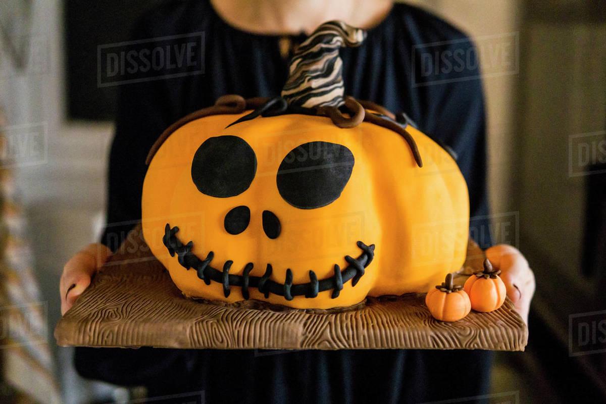 Black dressed woman carrying an halloween orange pumpkin sugar cake Royalty-free stock photo
