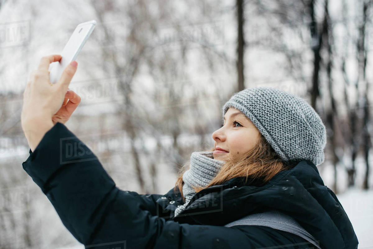 Young woman in hat and scarf with phone getting a selfie Royalty-free stock photo