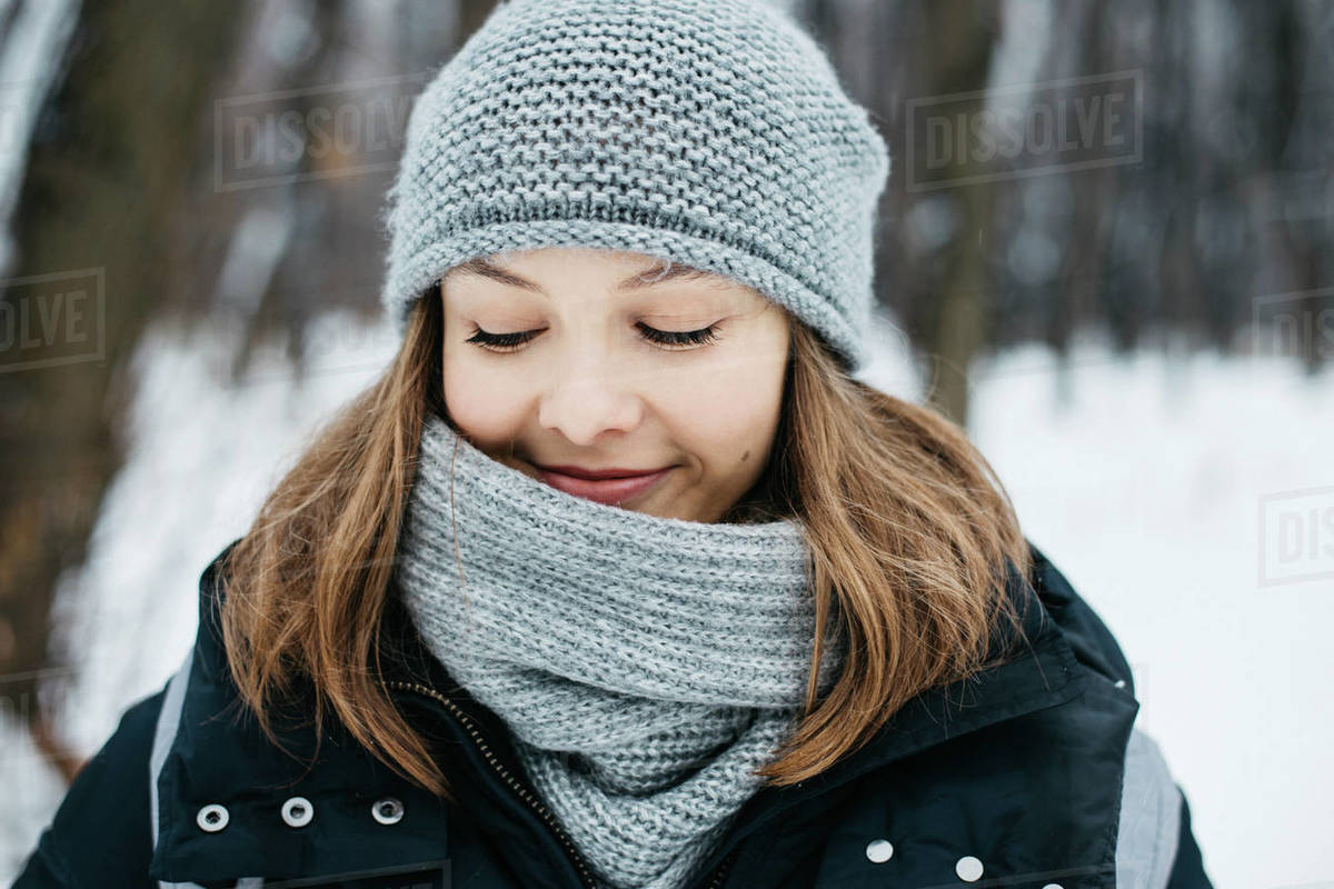 Happy young oman wearing hat and scarf walking in winter park Royalty-free stock photo
