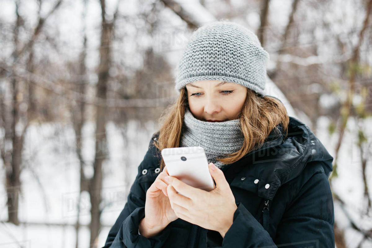 Young woman in hat with phone walking in winter park and texting Royalty-free stock photo