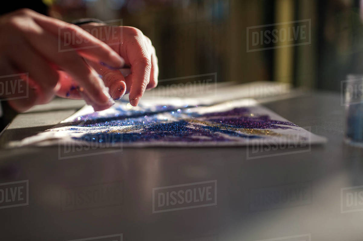 Close up of girls hands creating art with glitter Royalty-free stock photo