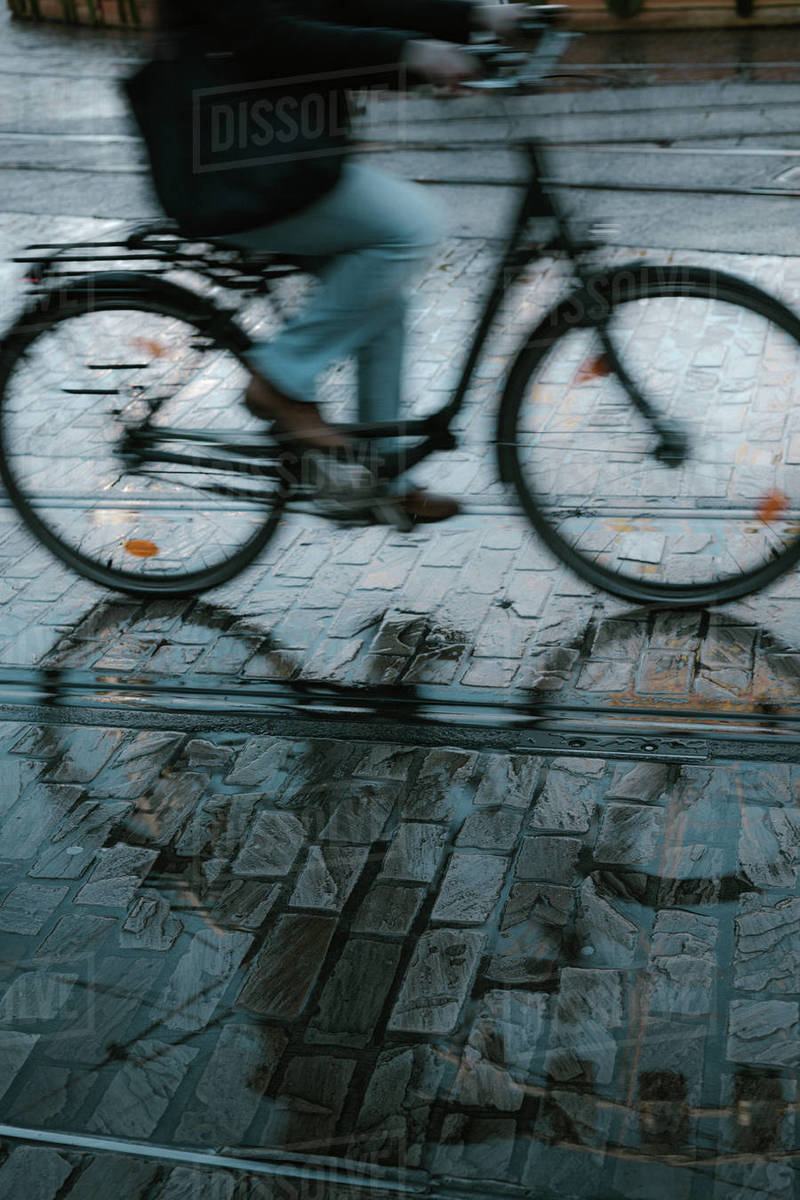 Motion blur of cyclist on reflective cobblestone streets Royalty-free stock photo