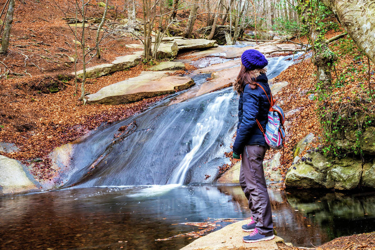 Woman standing watching falls in river Royalty-free stock photo