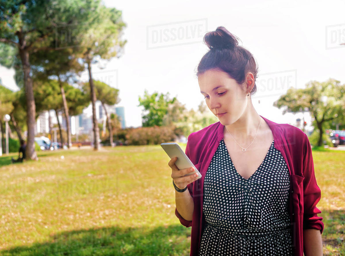 Serious young woman checking cell phone outdoors Royalty-free stock photo