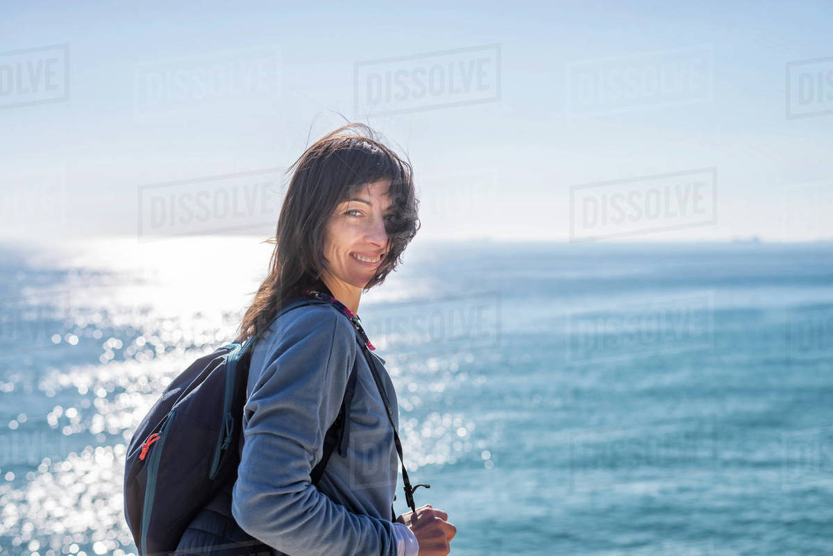 Beautiful woman standing against the sea looking camera and smiling Royalty-free stock photo