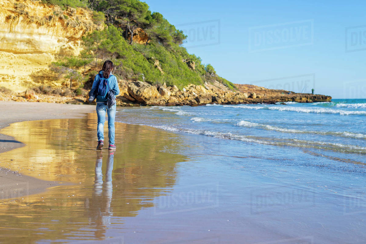 Back view of young woman with backpack walking on the beach Royalty-free stock photo