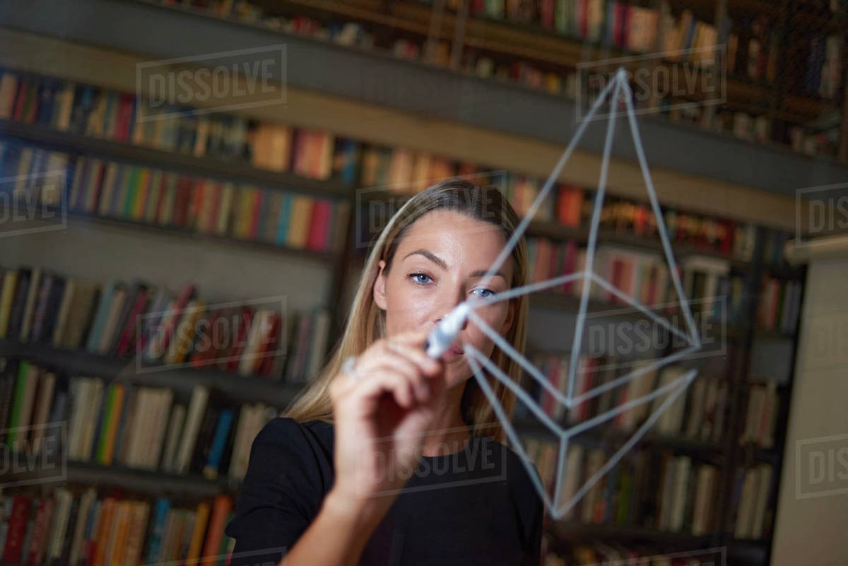 Young woman drawing the Ethereum logo on a window in the office Royalty-free stock photo