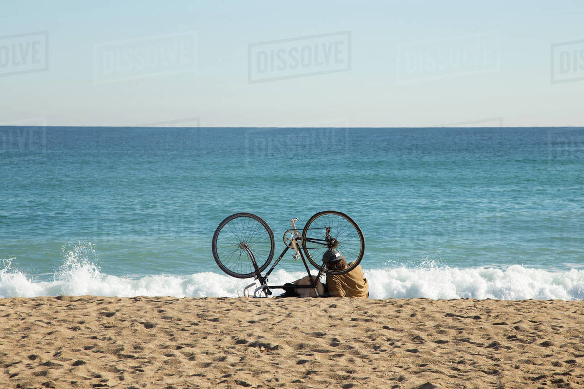 Young man reading in Barcelona beach Royalty-free stock photo