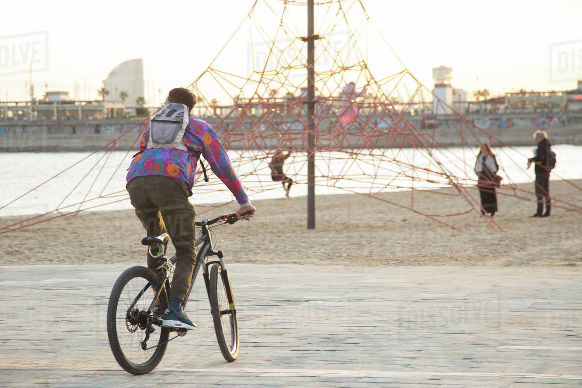 Young man riding a bike in Poblenou Beach Royalty-free stock photo