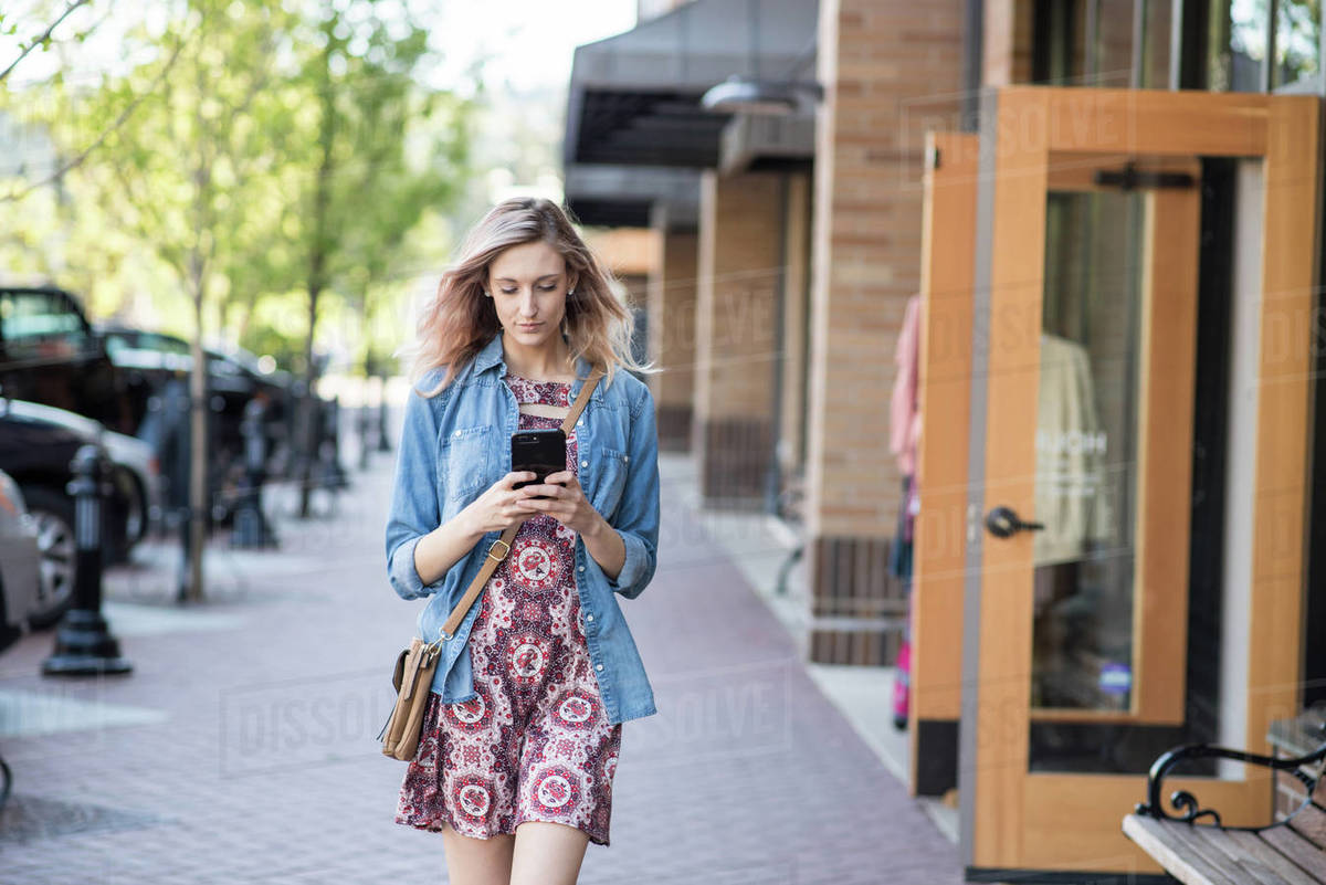 Woman texting on phone while walking down street Royalty-free stock photo
