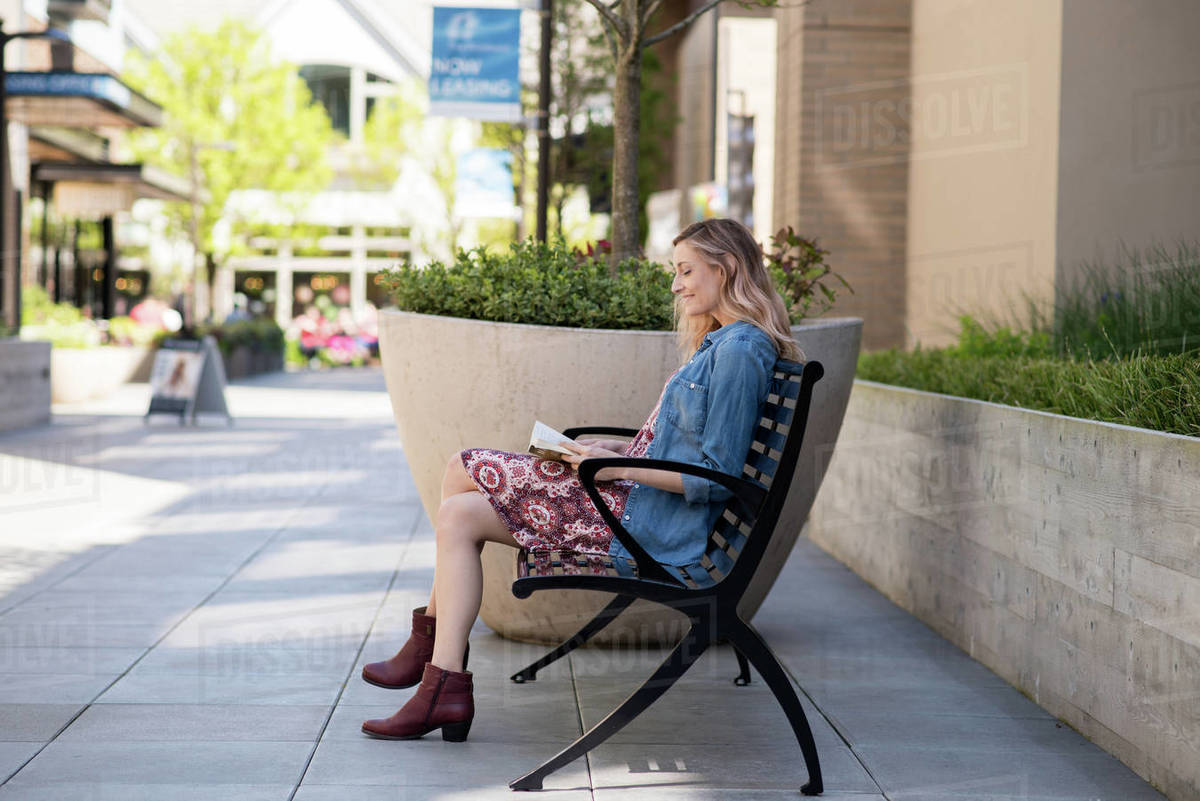Young woman reading book on bench in shopping district Royalty-free stock photo