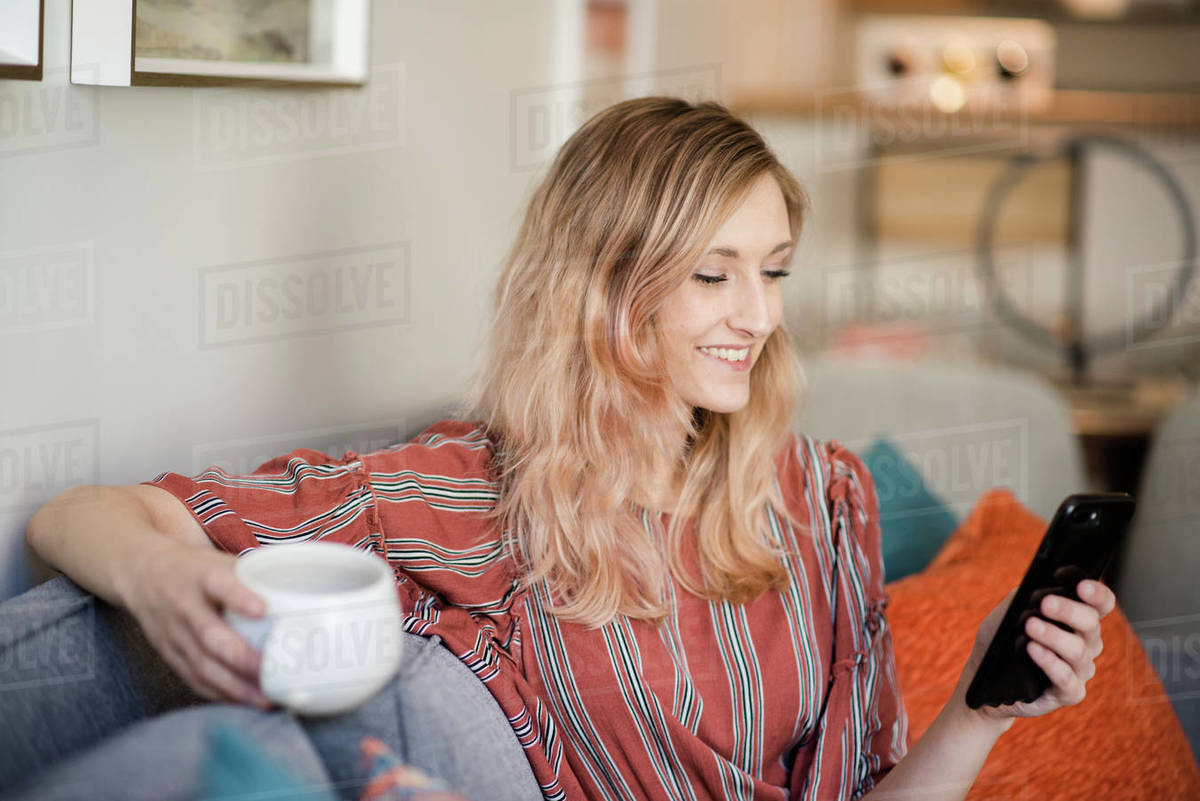 Woman sitting on couch using smart phone and smiling Royalty-free stock photo