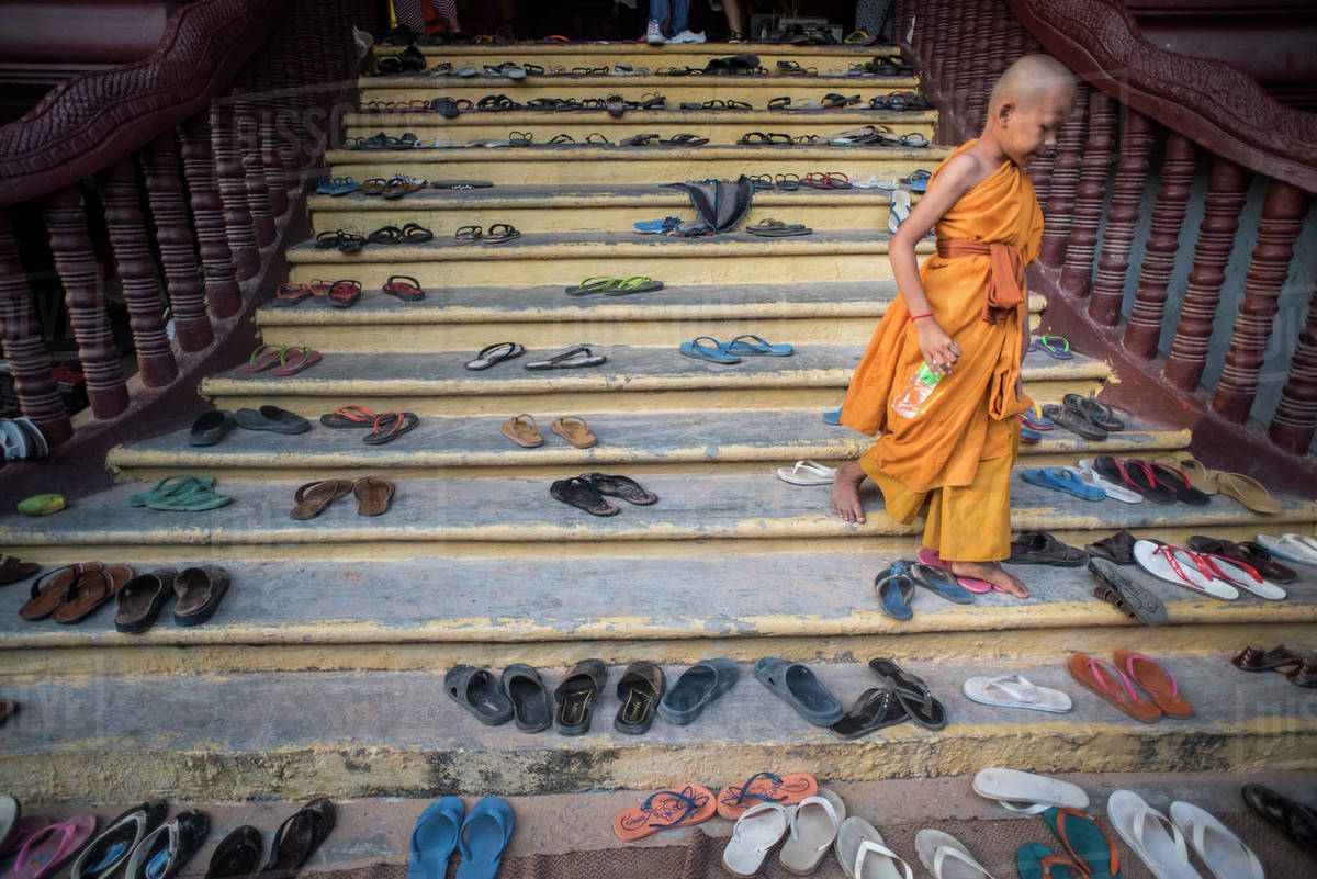 View of a buddhist monk using stairs full of platic sandals, Angkor Wat, Siem Reap, Cambodia. Royalty-free stock photo