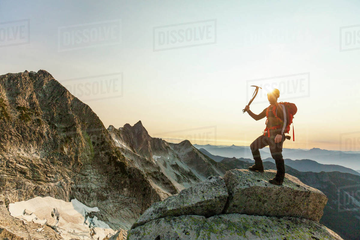 Climber holds ice axe, standing on a rocky mountain ridge Royalty-free stock photo