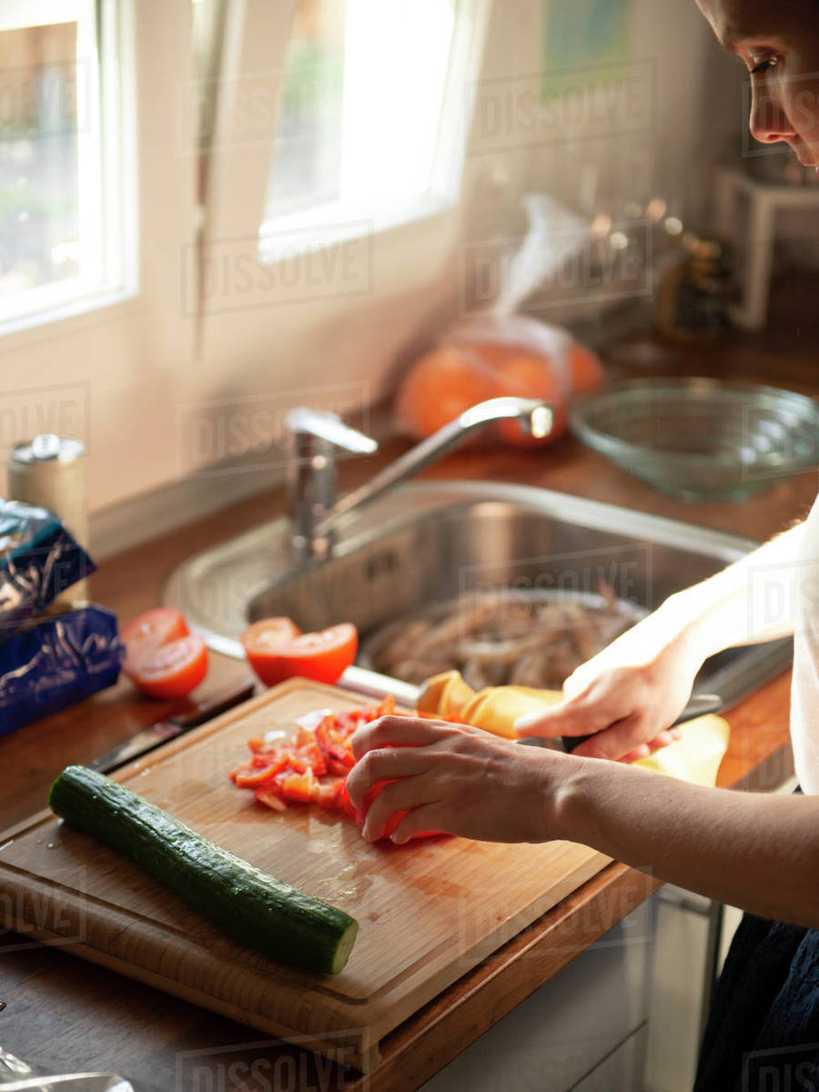 Young Woman Slicing Vegetables On Wooden Cutting Board For Salad Royalty-free stock photo