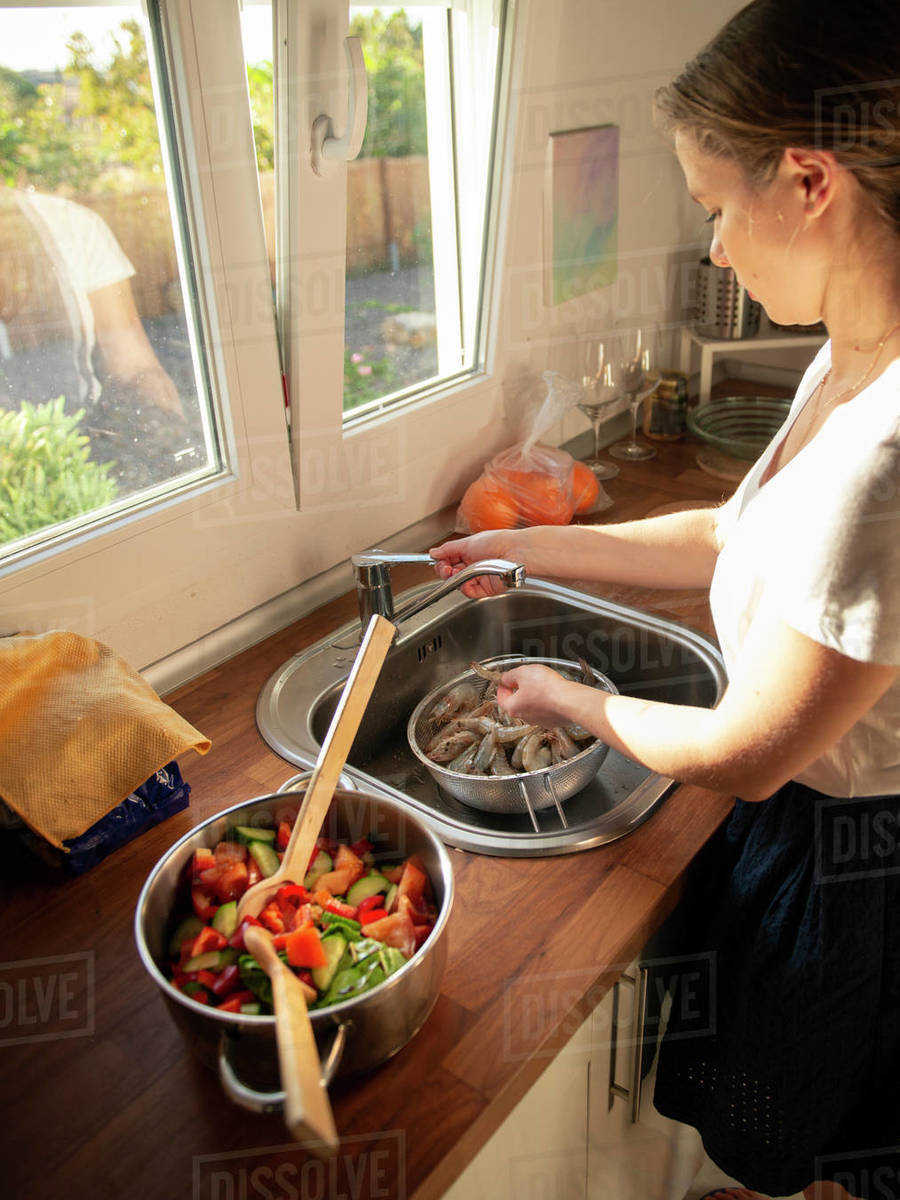 Young woman washing heap of raw shrimps in sink for cooking dinner Royalty-free stock photo