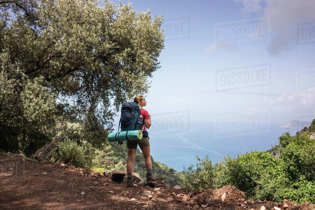 Young woman standing on mountain cliff and looking up against seascape Royalty-free stock photo