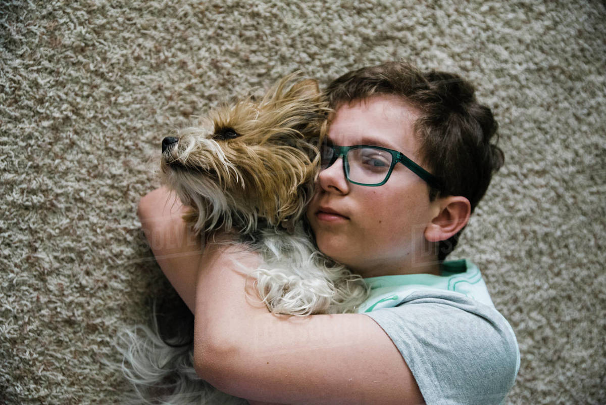 Tween together with his pet lying on the floor in the living room. Royalty-free stock photo