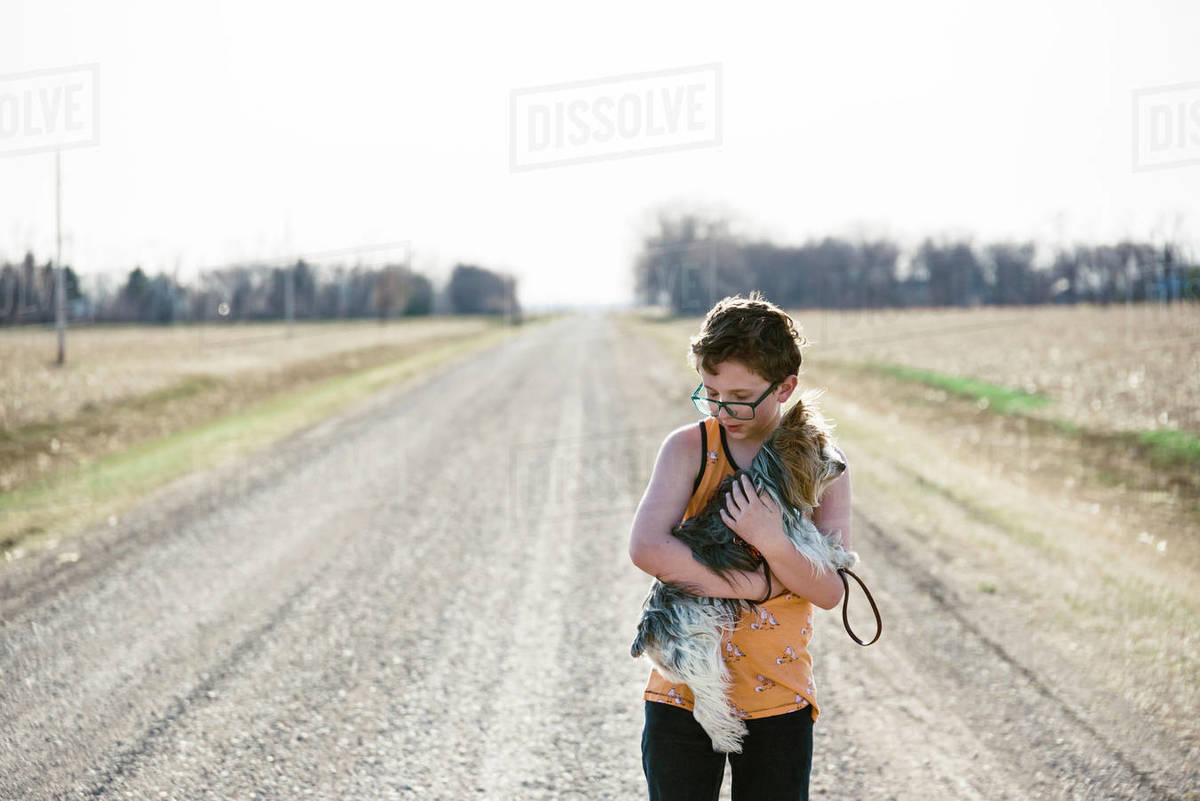 Boy holding his dog while exploring out on a dirt road. Royalty-free stock photo