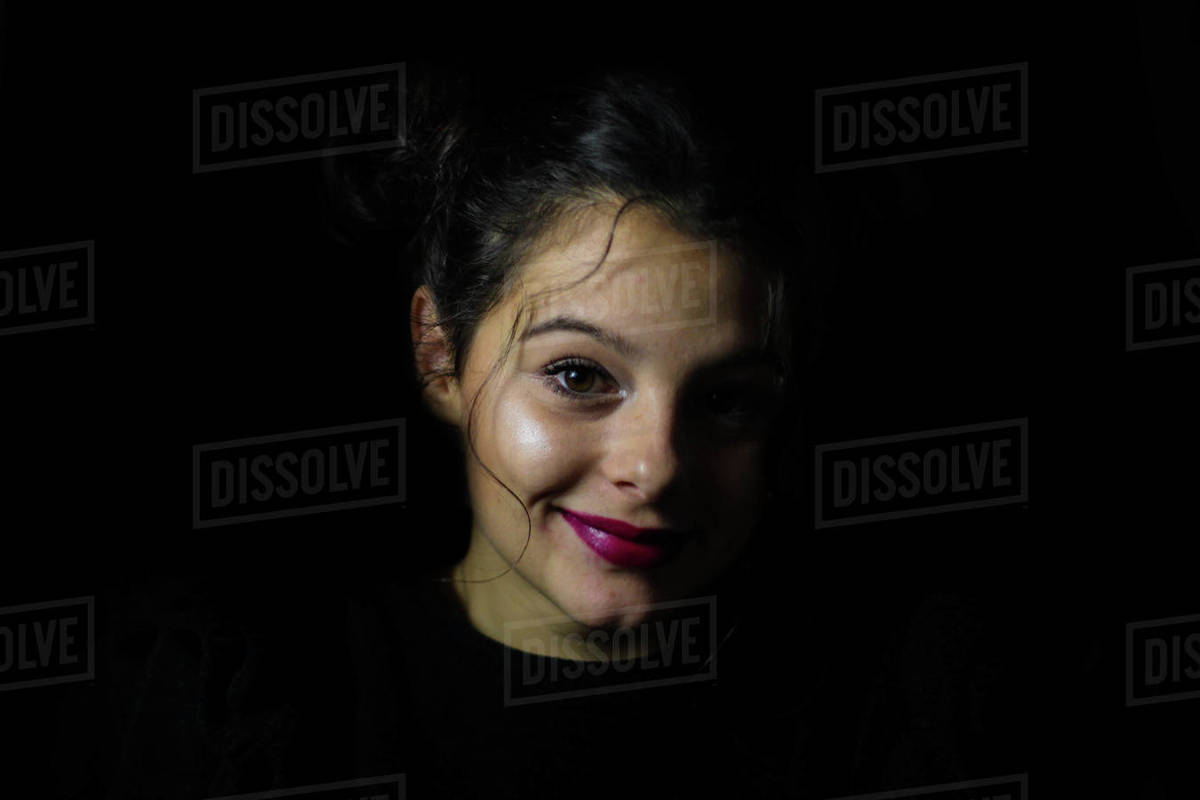 Pretty young smiling girl with bows in hair on black background Royalty-free stock photo