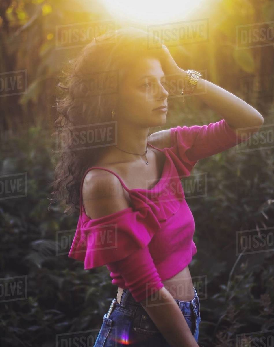 Pretty young girl with curly hair and pink shirt at sunset Royalty-free stock photo