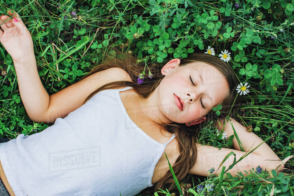 Young Girl with Daisy Flower Crown Resting in a Field of Clover Royalty-free stock photo