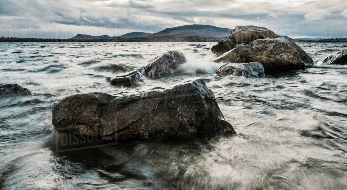 Waves crash into rocks on a lake in Maine on a stormy  and windy day Royalty-free stock photo