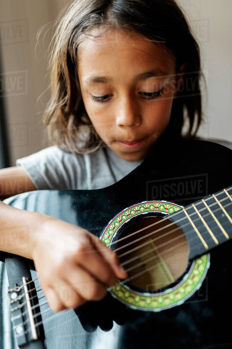 Long hair  boy playing guitar by the window at home Royalty-free stock photo