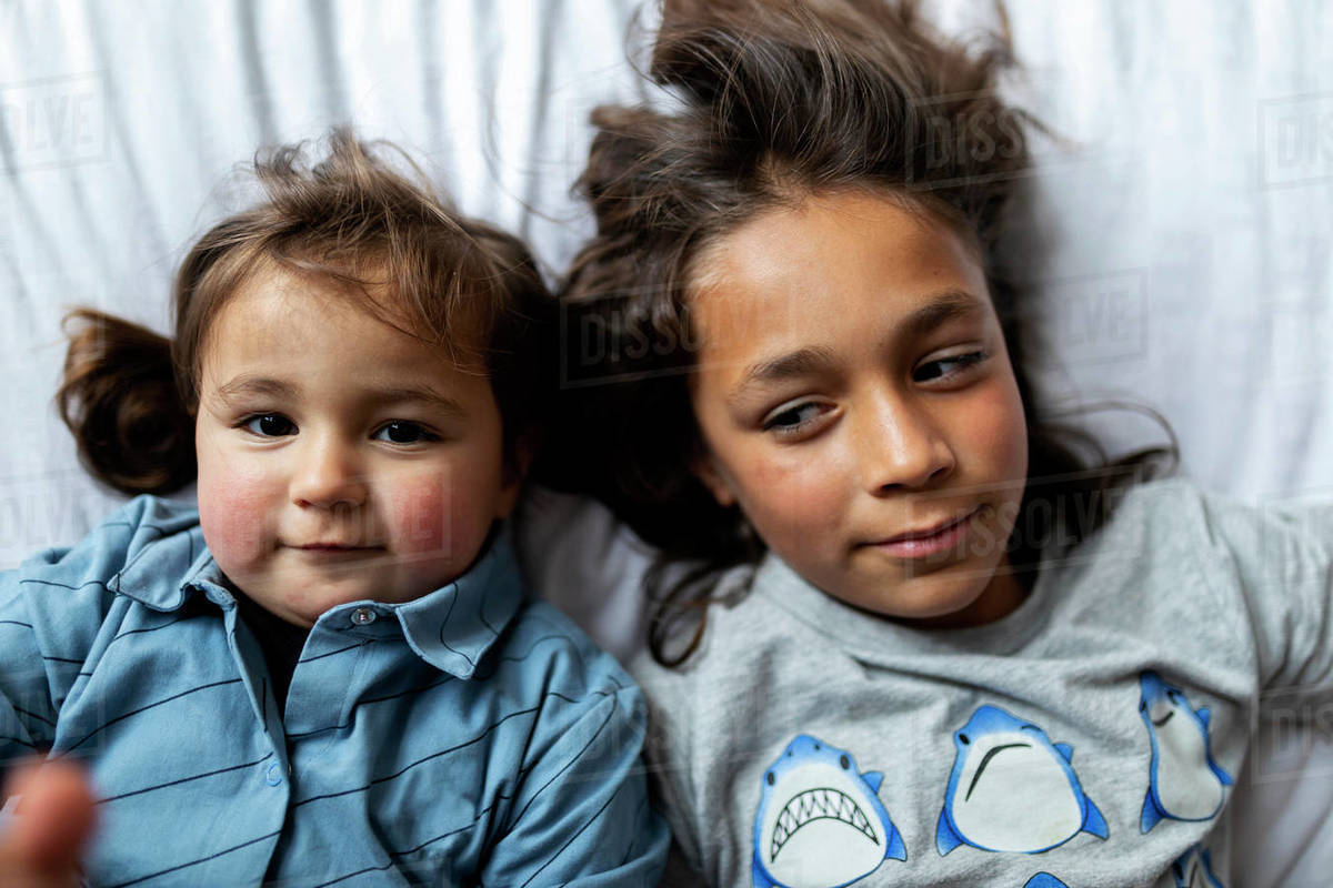 Siblings playing together on a bed Royalty-free stock photo