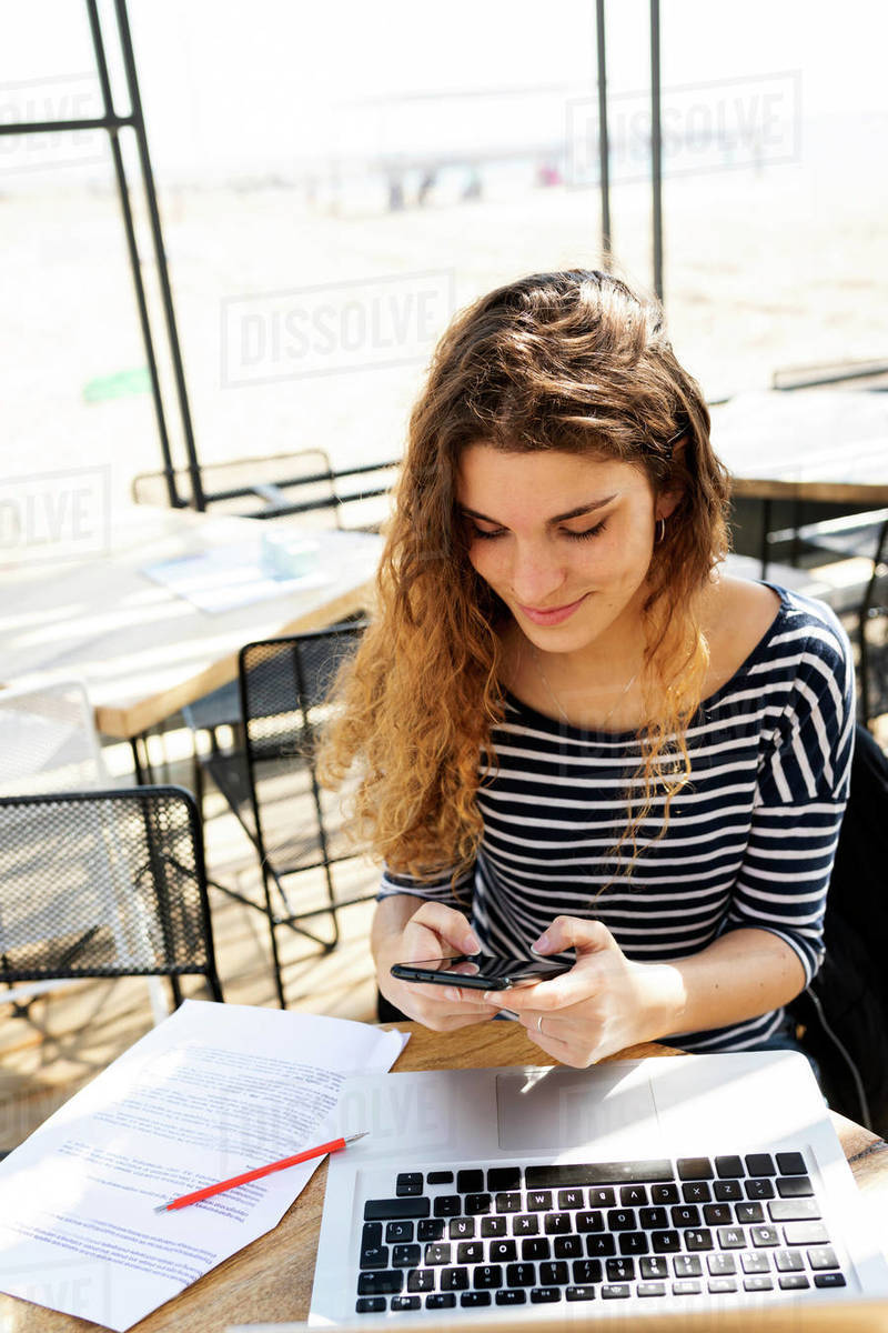 Woman texting and working with laptop on a terrace Royalty-free stock photo