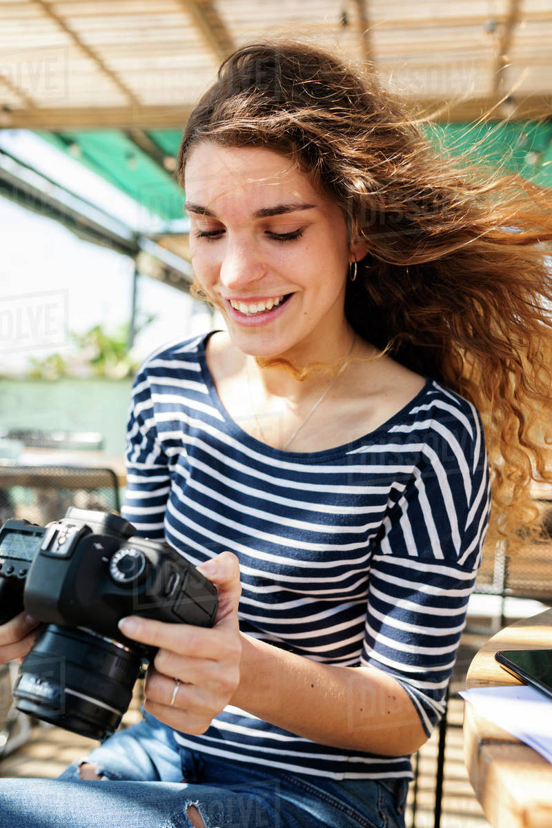 Brunette young woman on beach terrace checking her  camera Royalty-free stock photo