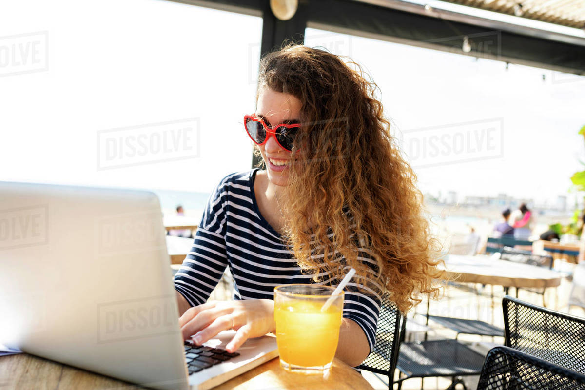 Young  woman working and drinking glass of orange juice Royalty-free stock photo